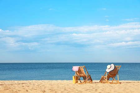 Lettini in legno vuoti e accessori da spiaggia sulla riva sabbiosa