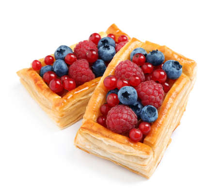 Fresh delicious puff pastry with sweet berries on white background
