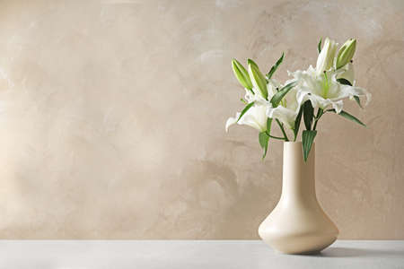 Vase with beautiful lilies on table against light brown background, space for text