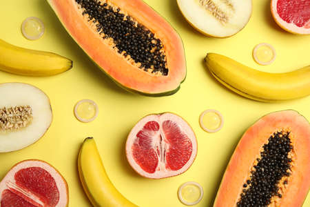 Flat lay composition with condoms and exotic fruits on yellow background. Erotic concept Archivio Fotografico
