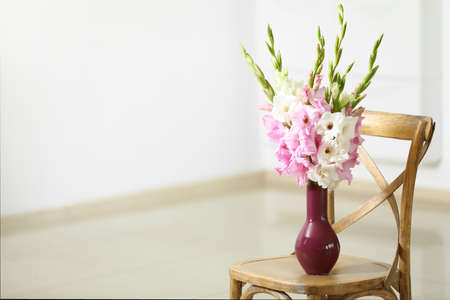 Vase with beautiful gladiolus flowers on wooden chair indoors. Space for text Stock fotó