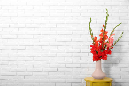 Vase with beautiful gladiolus flowers on wooden table against white brick wall. Space for text