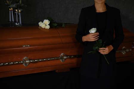 Junge Frau mit weißer Rose in der Nähe von Sarg im Bestattungsinstitut, Nahaufnahme