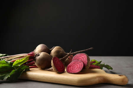 Wooden board with fresh beets on grey table against black background. Space for text