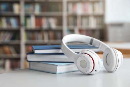 Stack of books and headphones on table in library