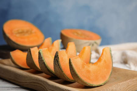 Slices of ripe cantaloupe melon in wooden tray on table