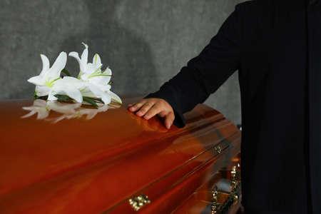 Junger Mann in der Nähe von Sarg mit weißen Lilien im Bestattungsinstitut