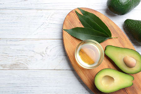 Board with bowl of natural oil and avocados on white wooden background, flat lay. Space for text