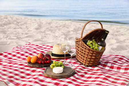 Checkered blanket with picnic basket and products on sunny beach Standard-Bild - 127796874