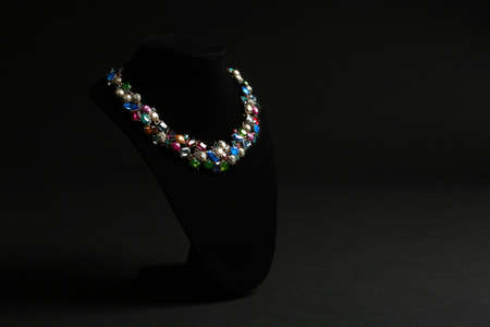 Elegant necklace on stand against black background, space for text. Luxury jewelry