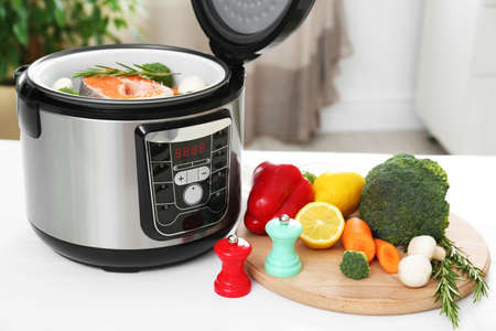 Modern multi cooker and products on kitchen table