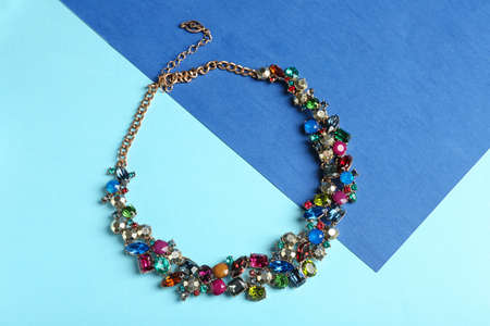 Elegant necklace on color background, top view. Luxury jewelry