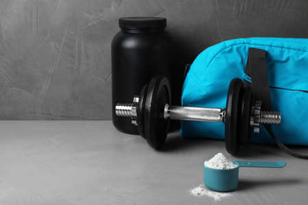 Composition with protein powder and dumbbell on table. Space for text