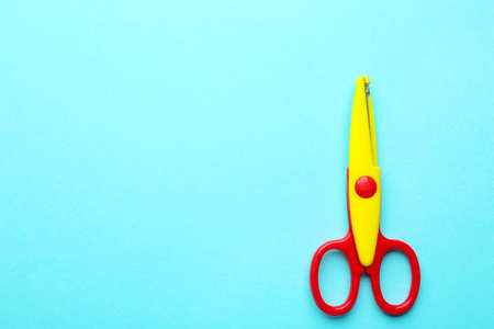 Decorative edge scissors on color background, top view. Space for text