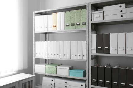 Carpetas con documentos en estantes en archivo Foto de archivo