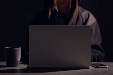 Woman with laptop and smartphone at table in darkness, closeup