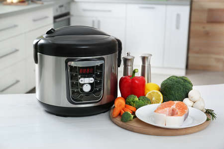 Modern multi cooker and products on kitchen table Stock Photo