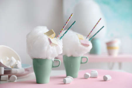 Cups of tasty cotton candy dessert and marshmallow on table, space for text