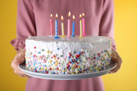 Woman holding birthday cake with burning candles on yellow background, closeup