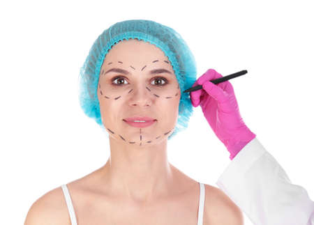Doctor drawing marks on womans face against white background. Cosmetic surgery