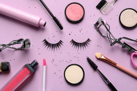 Composition à plat avec faux cils et autres produits de maquillage sur fond rose Banque d'images
