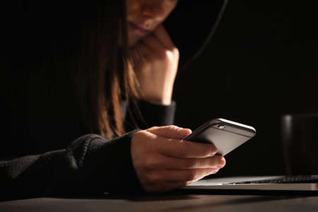 Woman using smartphone at table with laptop in darkness, closeup. Loneliness concept