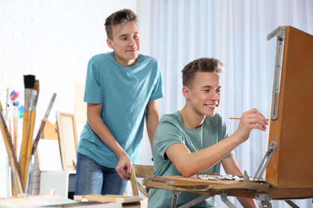 Teenage twin brothers having painting class in workshop. Hobby club Stockfoto