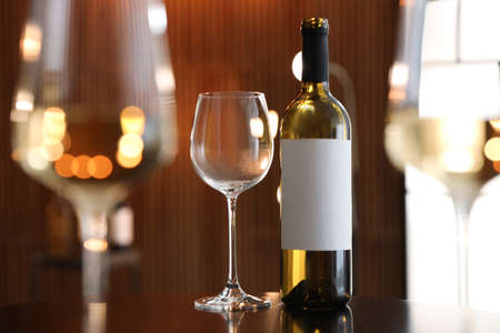 Bottle and glasses of wine on table against blurred background. Space for text Imagens