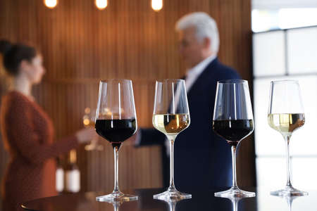 Glasses of different wines on table against blurred background Stock Photo