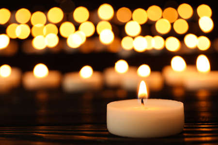 Burning candle on black table against blurred background, space for text