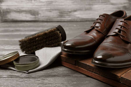 Footwear and shoe shine kit on grey table Stock Photo