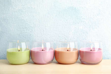 Burning wax candles in glass holders on wooden table, space for text