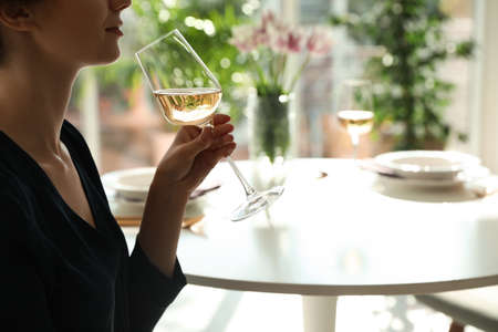 Woman with glass of wine in restaurant, closeup. Space for text