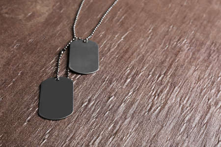 Blank military ID tags on brown textured background, space for text 写真素材