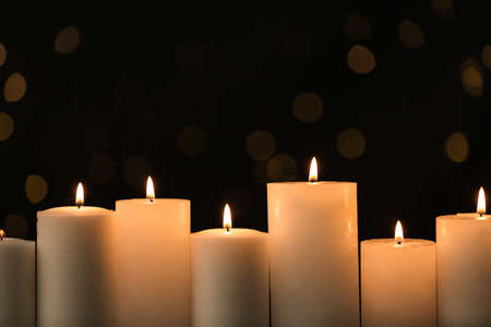 Burning candles on black background with blurred lights