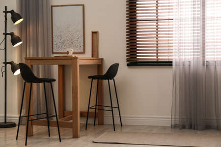Modern room interior with table set, window blinds and stylish decor elements