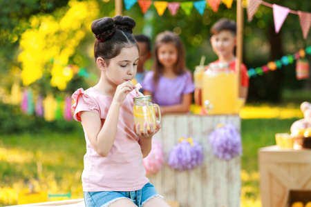 Cute little girl drinking natural lemonade in park, space for text. Summer refreshing beverage