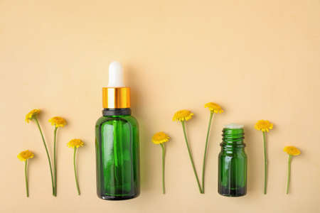 Bottles of essential oil and flowers on color background, flat lay