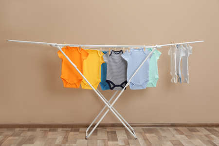 Different cute baby clothes hanging on clothes line near beige wall. Laundry day