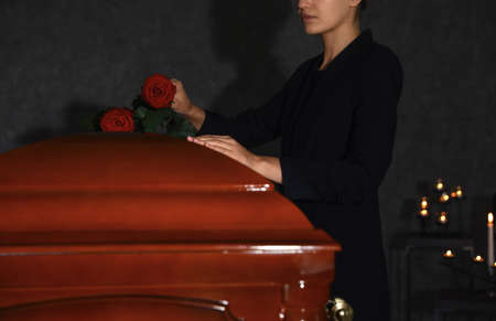 Young woman putting red rose onto casket lid in funeral home, closeup
