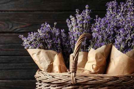 Fresh lavender flowers in basket against dark wooden background, closeup view