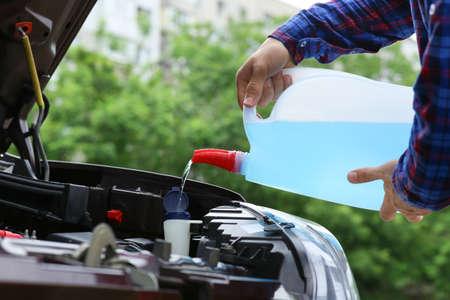 Man pouring liquid from plastic canister into car washer fluid reservoir, closeup Reklamní fotografie