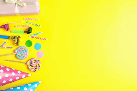 Flat lay composition with different birthday party items on yellow background, space for text