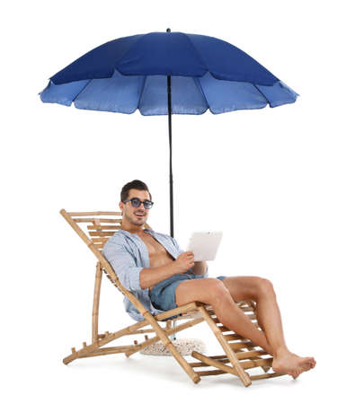 Young man with tablet on sun lounger under umbrella against white background. Beach accessories