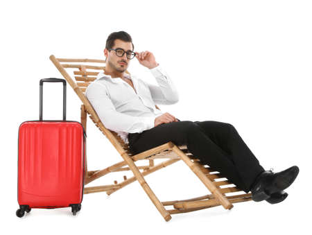 Young businessman with suitcase on sun lounger against white background. Beach accessories