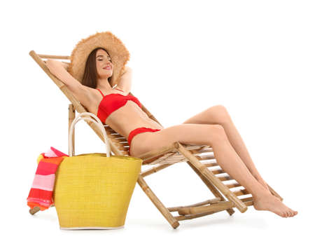 Young woman with beach accessories on sun lounger against white background