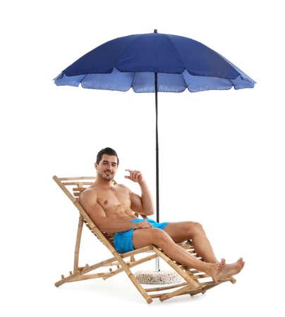 Giovane sulla sedia a sdraio sotto l'ombrellone su sfondo bianco. Accessori da spiaggia