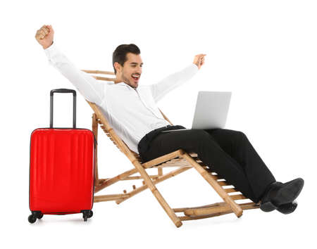 Young businessman with laptop and suitcase on sun lounger against white background. Beach accessories