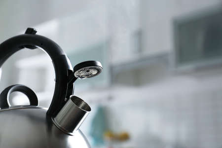Modern kettle with whistle in kitchen, space for text 写真素材