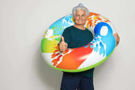 Funny mature man with bright inflatable ring on light background